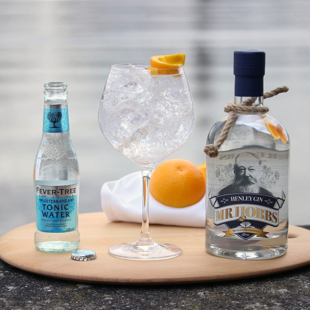 Gin bottle with mixers and an orange