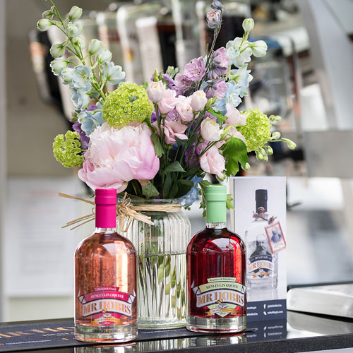 Mr Hobbs gin bottles on a bar with flowers